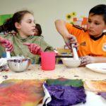 Kinder mit Mörsern bei der Herstellung der Farben