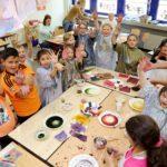 Kinder strecken die mit Farbe bekleckerten Hände in die Luft